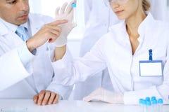 Lag av vetenskapliga forskare i laboratorium som studerar vikter eller blodprövkopian Ny vaccin för farmakologiindustr Arkivfoto