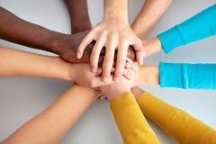 Lag av vänner som tillsammans visar enhet med deras händer Arkivfoton