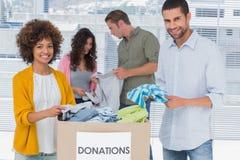 Lag av volontärer som ut tar kläder från en donationask Arkivbild