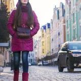 Lag, hatt och halsduk för vinter för lilor för nätt brunettflicka som bärande går vid den europeiska gatan på vintern Royaltyfri Bild