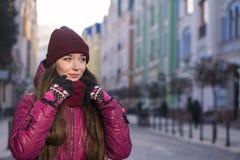 Lag, hatt och halsduk för vinter för lilor för nätt brunettflicka som bärande går vid den europeiska gatan på vintern Arkivfoton