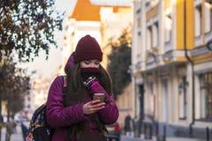 Lag, hatt och halsduk för vinter för lilor för nätt brunettflicka som bärande går vid den europeiska gatan på vintern, genom att  Royaltyfri Foto