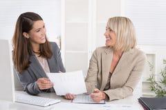 Lag: lyckat sammanträde för affärskvinna två på skrivbordet som har gyckel på Arkivfoton