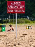 Laga beach poster for dangerous area for bathers. Laga wild beach with sign of Dangerous area for bathers, Bizkaia, Basque Country Royalty Free Stock Images