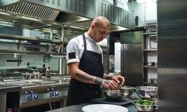 laga mat älskar jag Manlig kock i förkläde, med svarta tatueringar på hans armar som förbereder sallad i ett restaurangkök royaltyfria foton
