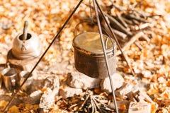 Laga mat över en lägereld i en gjutjärnkruka Gjutjärnkruka för soppa som hänger över brandlägerelden Royaltyfri Fotografi