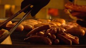 Laga mat att ta bröd och korvar från varmt galler i aftonen 4K sköt länge arkivfilmer