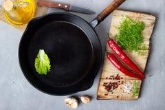 Laga mat bakgrundsbegreppet - tomma järnpanna, skärbräda och kryddor på en grå färgstenbakgrund royaltyfri foto
