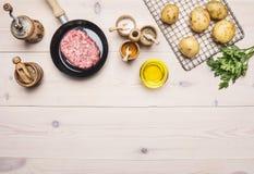 Laga mat den hemlagade hamburgaren med stekte potatisar, nytt jordnötkött i en liten pannapersilja, olika kryddor på vit träta Royaltyfri Bild