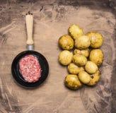 Laga mat den hemlagade hamburgaren med stekte potatisar, nytt jordnötkött i slut för bästa sikt för bakgrund för liten stekpanna  Royaltyfria Bilder