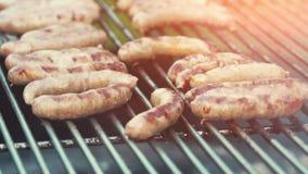 Laga mat för BBQ/som röker läckra saftiga köttbiffar och korvar på gallret lager videofilmer