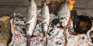 Laga mat fisken som grillas över varm kolbrasa arkivbilder
