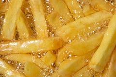Laga mat franska småfiskar i oljanärbild, bakgrund Potatis som steker med bubblan arkivbild