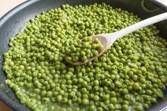 Laga mat gröna ärtor i svart stekpanna med träskeden Royaltyfri Bild