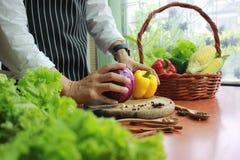 Laga mat händer som rymmer blomkålen och gul spansk peppar i köksbord arkivfoton