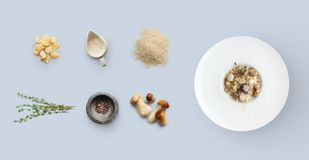 Laga mat ingredienser för italiensk risotto med lösa champinjoner som isoleras på blått Royaltyfria Bilder
