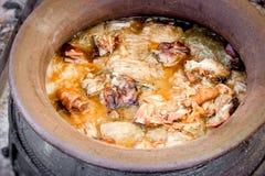 Laga mat knogen, hock, skinkahock, grisköttknä, grisköttskuldran och kål in i jordnära kokkärl-pannor royaltyfria foton
