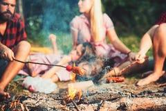 Laga mat korvar på pinnar över flammor av lägereld, över natten campa i sommar Grupp av vänner som sitter vid brasan royaltyfri fotografi