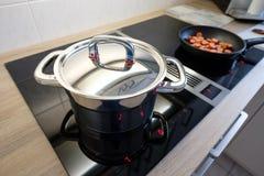 Laga mat krukan med krom pläterade locket på en cooktop Arkivfoto
