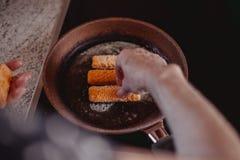 Laga mat läckra fiskpinnar i panna royaltyfri foto