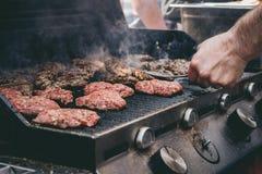 Laga mat läckra saftiga kötthamburgare på det utomhus- gallret Arkivbild