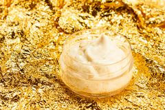 Laga mat med grädde med guld i en krus på en guld- bakgrund arkivbilder