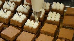 Laga mat med grädde sammanpressning på chokladkakor Sammanpressning av krämen på kakan lager videofilmer