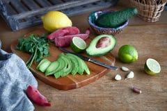 Laga mat mexikansk matguacamole - avokado, limefrukt, citron, peppar, vitlök och koriander på en trätabell royaltyfri foto