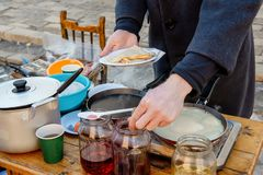Laga mat pannkakor som är utvändiga i förkylningen Pannkakor stekas i en panna, och ånga kommer ut ur dem avsked som övervintrar  royaltyfria foton