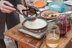 Laga mat pannkakor som är utvändiga i förkylningen Pannkakor stekas i en panna, och ånga kommer ut ur dem avsked som övervintrar  arkivfoto