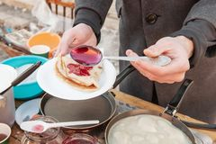 Laga mat pannkakor som är utvändiga i förkylningen Pannkakor stekas i en panna, och ånga kommer ut ur dem avsked som övervintrar  arkivbild