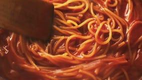Laga mat pasta i sås i panna och omrörning arkivfilmer