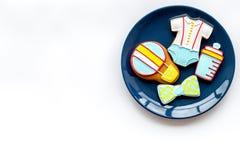 Laga mat pepparkakakakor på plattan för baby shower på den vita modellen för den bästa sikten för bakgrund royaltyfria bilder