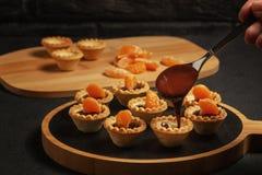 Laga mat söta tartlets med tangerinskivor - hällande smältt choklad royaltyfria foton