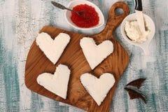 Laga mat smörgåsar med den röda kaviaren och gräddost i formen av en hjärta för valentin dag royaltyfri foto
