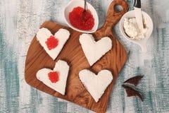 Laga mat smörgåsar med den röda kaviaren och gräddost i formen av en hjärta för valentin dag arkivbild
