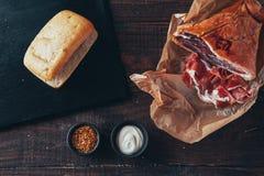 Laga mat smaklig panini med skinka som täckas med ost, tomater och att smaksätta arkivbilder
