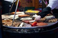 Laga mat snabbmat på ett enormt galler på mässan arkivbild