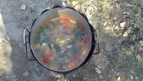 Laga mat soppan över en öppen brand Arkivfoto