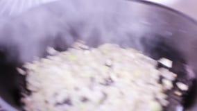 Laga mat stekte lökar i en panna arkivfilmer