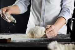Laga mat strilar deg med mjöl på köksbordet royaltyfria bilder