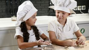 laga mat tillsammans Två barn i rullande deg för kockhatt i hem- kök Lekrestaurang för två ungar 4K arkivfilmer