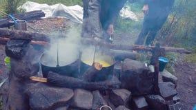 Laga mat utomhus- mat i turist- kruka på brasan Bearbeta att förbereda campa mat på bränningbrand, medan fotvandra till löst arkivfilmer