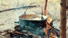Laga mat utomhus- mat i turist- kruka på brasan Process som förbereder campa mat arkivfilmer