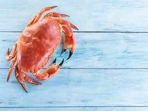 Lagad mat brun krabba eller ätlig krabba på den blåa träfliken arkivfoto