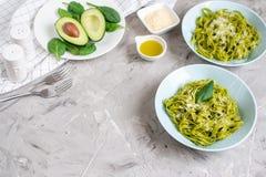 Lagad mat grön spenattagliatellepasta på en platta med parmesanost och avokadosås, Italien mat arkivfoton