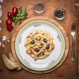 Lagad mat paella med den havs- maträtten på en skärbräda med bröd kryddade med örter och tomater en gaffel på lantlig träbackg Royaltyfria Bilder