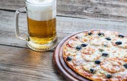 Lagad mat pizza med ett exponeringsglas av öl Royaltyfri Foto