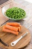 Lagade mat gröna ärtor med den lagade mat moroten på träbrädet Arkivfoto