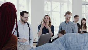 Lagande på den sunda arbetsplatsen Lycklig ung framstickandeaffärsman som leder det moderna kontoret som möter RÖD EPOS för ultra stock video